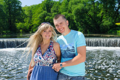 Cute couple in the park on a sunny day. Beautiful happy mature couple hugging near river waterfall at summer day. Happy guy and girl Stock Images
