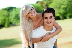 Cute couple piggybacking outdoors. Stock Photo
