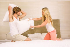 Cute couple pillow fighting on their bed Stock Photography