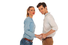 Cute couple posing holding hands. And facing each other while looking at the camera in studio background stock images