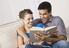 Cute Couple Reading and Laughing Together Royalty Free Stock Image