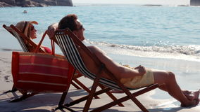 Cute couple relaxing on beach chair. Video of cute couple relaxing on beach chair at the beach stock footage