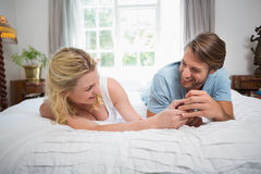 Cute couple relaxing on bed laughing together Stock Images
