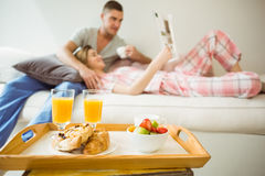 Cute couple relaxing on couch at breakfast Stock Images