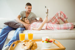 Cute couple relaxing on couch at breakfast Royalty Free Stock Images
