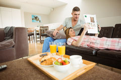 Cute couple relaxing on couch at breakfast Royalty Free Stock Photo