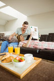 Cute couple relaxing on couch at breakfast Stock Image