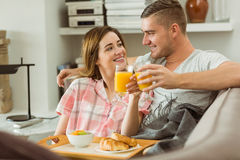 Cute couple relaxing on couch with breakfast Royalty Free Stock Photos