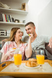 Cute couple relaxing on couch with breakfast Stock Image