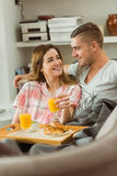 Cute couple relaxing on couch with breakfast Stock Photo