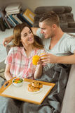 Cute couple relaxing on couch with breakfast Stock Photos