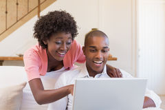 Cute couple relaxing on couch with laptop Royalty Free Stock Photography