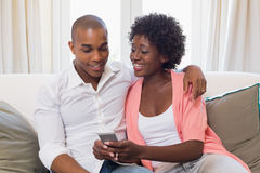 Cute couple relaxing on couch with smartphone Stock Image