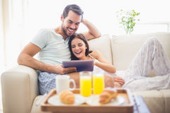 Cute couple relaxing on couch with tablet at breakfast stock photos
