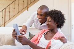 Cute couple relaxing on couch with tablet pc Royalty Free Stock Images