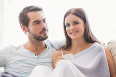 Cute couple relaxing on couch under blanket Royalty Free Stock Image