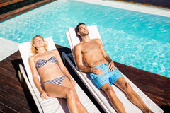 Cute couple relaxing on deckchairs Stock Photography