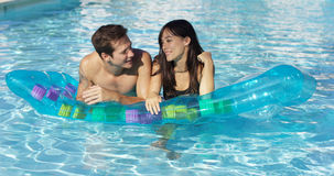 Cute couple relaxing on floating mattress in pool Stock Photos
