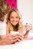 Cute couple relaxing on their bed and having coffee Stock Image