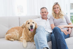 Cute couple relaxing together on the couch with their dog Royalty Free Stock Images