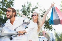 Cute couple riding a scooter Stock Photos