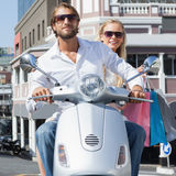 Cute couple riding a scooter royalty free stock images