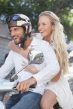 Cute couple riding a scooter Stock Image