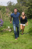 Cute couple running holding hands Royalty Free Stock Photography