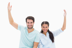 Cute couple sitting with arms raised Stock Image