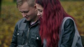 Cute couple sitting on a bench in autumn park and using a digital tablet together. Young woman with red hair and. Attractive man in a leather jacket discussing stock footage