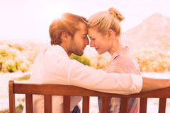 Cute couple sitting on bench together smiling at each other Royalty Free Stock Photos