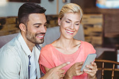 Cute couple sitting in cafe looking at smartphone Royalty Free Stock Photos