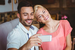 Cute couple sitting in cafe looking at smartphone Royalty Free Stock Photography