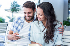 Cute couple sitting in cafe looking at smartphone Stock Photos