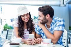 Cute couple sitting in cafe looking at smartphone Stock Photography