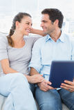 Cute couple sitting on the couch using tablet pc Royalty Free Stock Photo