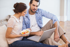Cute couple sitting on floor using laptop Stock Photography