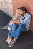 Cute couple sitting on ground Stock Photos