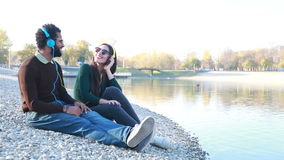 Cute couple sitting by lake and listening to music with headphones. Cute young couple sitting by lake and listening to music with headphones in autumn stock footage