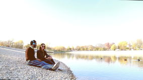 Cute couple sitting by lake and listening to music with headphones. Cute young couple sitting by lake and listening to music with headphones in autumn, graded stock video