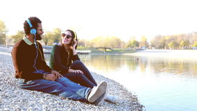 Cute couple sitting by lake and listening to music with headphones. Cute young couple sitting by lake and listening to music with headphones in autumn, slow stock video