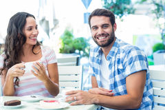 Cute couple sitting outside at a cafe with man smiling at camera Royalty Free Stock Photography