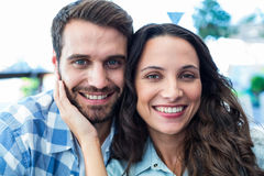 Cute couple sitting outside a cafe smiling at camera Royalty Free Stock Photos