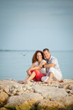 Cute Couple Sitting on Rocks at the Beach Stock Image