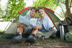 Cute couple sitting by tent reading a map smiling at camera Royalty Free Stock Images
