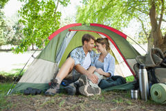Cute couple sitting in their tent showing affection Stock Photography