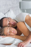 Cute couple sleeping and spooning in bed Stock Photos
