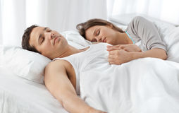 Cute couple sleeping together on their bed. At home Stock Images