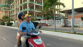 Parents with their little kid riding motorcycle on sunny city street stock footage