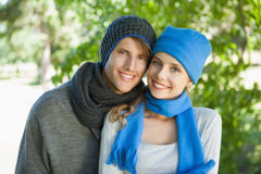 Cute couple smiling at camera in hats and scarves Stock Image